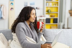 Woman sitting on cozy couch sipping tea